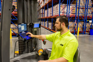 Warehouse worker using management system technology on the forklift